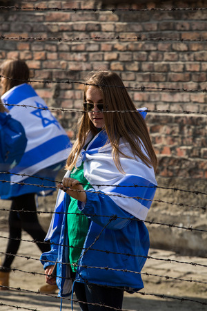 nazi flag: OSWIECIM, POLAND - APRIL 16, 2015:the next generation of people from the all the world meets on the March of the Living in german Concentration Camp in Auschwitz Birkenau.Poland