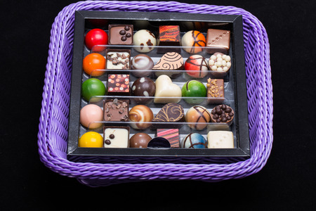 temptation: Set of a various chocolate pralines in lavender basket Stock Photo