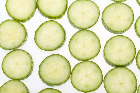obscured face: Freshly sliced cucumber  isolated on white background Stock Photo