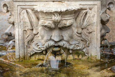 spew: Marble fountain in the shape of the head of a man in the gardens of Villa  Borghese, Rome, Italy.
