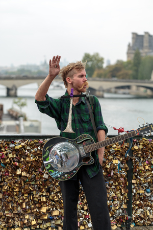 busker: PARIS, FRANCE - SEPTEMBER 11, 2014: A street musician busker entertain public on Pont des Arts in Paris, France Editorial