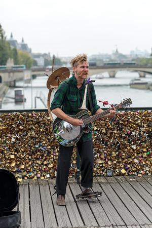 entertain: PARIS, FRANCE - SEPTEMBER 11, 2014: A street musician busker entertain public on Pont des Arts in Paris, France Editorial