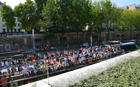tour boats: PARIS, FRANCE - SEPT 8, 2014: View of the Seine River with cruise tour boats. In Paris there are several boat tourist trips across the Seine to show tourists the sights of interest. Editorial