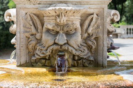 Marble fountain in the shape of the head of a man in the gardens of Villa  Borghese, Rome, Italy.