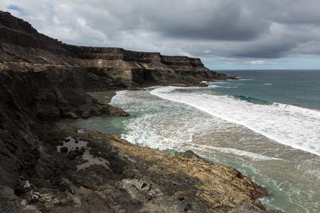 Wave splashing over a rock on the beach of Puertito de los Molinos on Fuerteventura. Canary Island, Spain