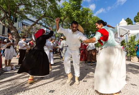 FUNCHAL, PORTUGAL - SEPTEMBER 1, 2015: Dancers with local costumes demonstrating a folk dance during the Wine Festival in Funchal on the Madeira, Portugal.