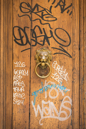 grungey: Old wooden door covered with graffiti  in Trastevere district. Rome, Italy.
