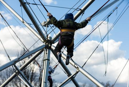 bungee jumping: Los niños se divierten saltando en el trampolín del amortiguador auxiliar atada con gomas Foto de archivo