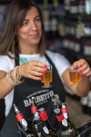 FUNCHAL, MADEIRA, PORUGAL - SEPTEMBER 3, 2016:  Wine producers encourage to the tasting of their wines during Madeira wine Festival in Funchal on Madeira, Portugal, Editorial