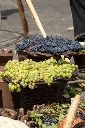 bunches of white and black grapes in a wicker basket.