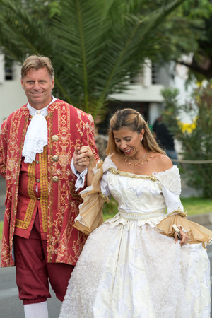 solemnize: FUNCHAL, MADEIRA, PORTUGAL - SEPTEMBER 4, 2016:  Group of people in historical fashion dress durnig historical and ethnographic  parade of Madeira Wine Festival in Funchal. Madeira, Portugal