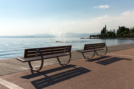 lakeshore: Empty benches on lakeshore of Garda lake, Bardolino, Italy
