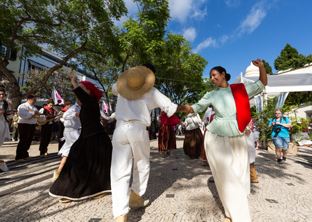 ensemble: FUNCHAL, PORTUGAL - SEPTEMBER 1, 2016: Dancers with local costumes demonstrating a folk dance during the Wine Festival in Funchal on the Madeira, Portugal.