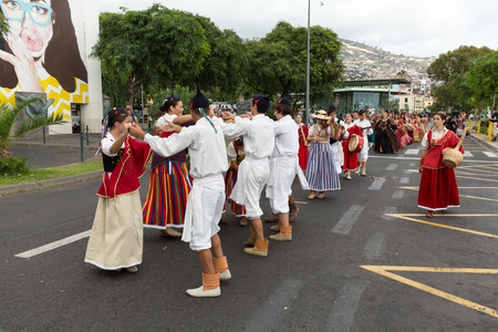 ensemble: FUNCHAL, PORTUGAL - SEPTEMBER 4, 2016: Dancers with local costumes perform a folk dance during the parade of Wine Festival in Funchal on the Madeira, Portugal.