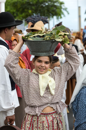 ethnographic: FUNCHAL, MADEIRA, PORTUGAL - SEPTEMBER 4, 2016: Woman carry the baskets of grapes in traditional costume  durnig historical and ethnographic  parade of Madeira Wine Festival in Funchal. Madeira, Portugall