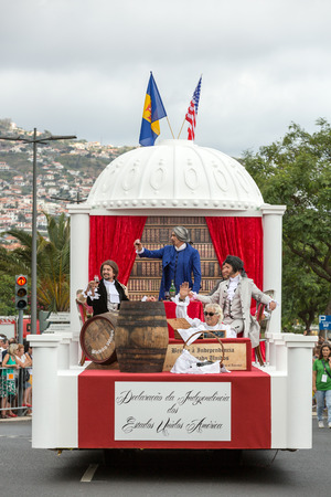 ethnographic: FUNCHAL, MADEIRA, PORTUGAL - SEPTEMBER 4, 2016: Men in historical fashion dress raise toasts durnig historical and ethnographic  parade of Madeira Wine Festival in Funchal. Madeira, Portugal
