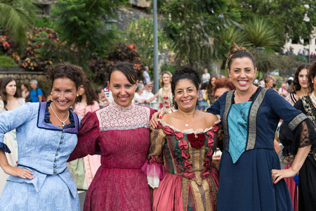 ethnographic: FUNCHAL, MADEIRA, PORTUGAL - SEPTEMBER 4, 2016:  Group of women in historical fashion dress durnig historical and ethnographic  parade of Madeira Wine Festival in Funchal. Madeira, Portugal