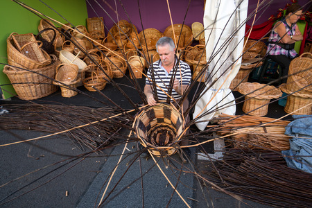 basketry: CAMACHA, MADEIRA, PORTUGAL - SEPTEMBER 10, 2016:  A basket weaver at work in the factory shop in Camacha Madeira Portugal Editorial