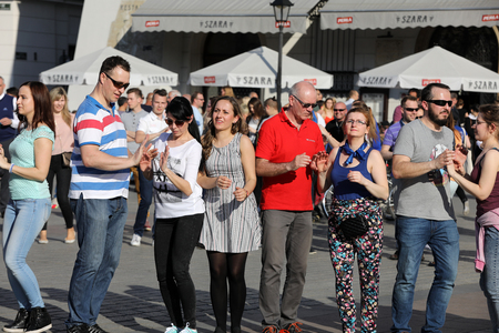 rythm: CRACOW, POLAND - APRIL 1, 2017: International Flashmob Day of Rueda de Casino, 57 countries, 160 cities. Several hundred persons dance Hispanic rhythms on the Main Square in Cracow. Poland Editorial