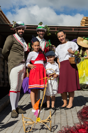 ethnographic: ESTREITO DE CAMARA DE LOBOS, PORTUGAL - SEPTEMBER 10, 2016:  Family wearing in traditional costumes at Madeira Wine Festival in Estreito de Camara de Lobos, Madeira, Portugal. The Madeira Wine Festival honors the grape harvest with a celebration of tradit Editorial