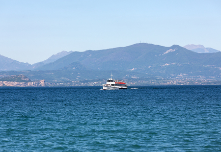 frequented:  Ferry boat on  Lake Garda. Garda Lake is one of the most frequented tourist regions of Italy.  Stock Photo