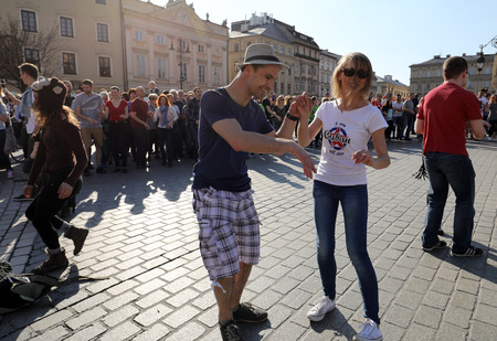 CRACOW, POLAND - APRIL 2, 2016: International Flashmob Day of Rueda de Casino, 57 countries, 160 cities. Several hundred persons dance Hispanic rhythms on the Main Square in Cracow. Poland