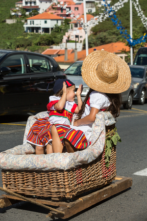 ESTREITO DE CAMARA DE LOBOS, PORTUGAL - SEPTEMBER 10, 2016: Two children wearing in traditional costumes at Madeira Wine Festival in Estreito de Camara de Lobos, Madeira, Portugal. The Madeira Wine Festival honors the grape harvest with a celebration of t