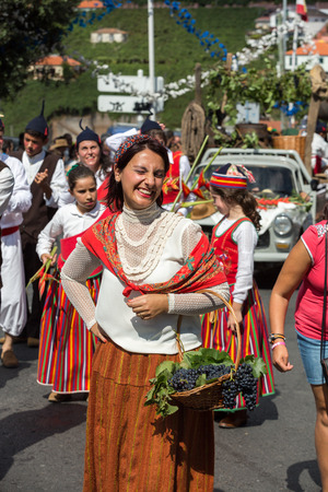 historical events: ESTREITO DE CAMARA DE LOBOS, PORTUGAL - SEPTEMBER 10, 2016: People wearing in traditional costumes at Madeira Wine Festival in Estreito de Camara de Lobos, Madeira, Portugal. The Madeira Wine Festival honors the grape harvest with a celebration of traditi