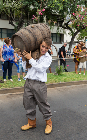 historical events: FUNCHAL, MADEIRA, PORTUGAL - SEPTEMBER 4, 2016: Man carry the barrel of wine in traditional costume  durnig historical and ethnographic  parade of Madeira Wine Festival in Funchal. Madeira, Portugal