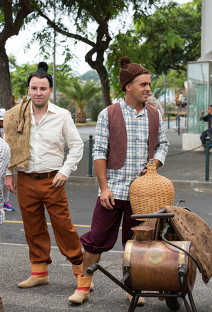 historical events: FUNCHAL, PORTUGAL - SEPTEMBER 4, 2016: Two men in traditional costume  durnig historical and ethnographic  parade of Madeira Wine Festival in Funchal. Madeira, Portugal Editorial