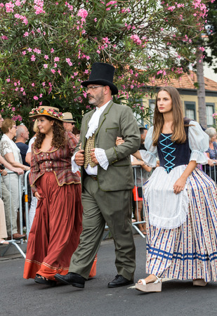 historical events: FUNCHAL, MADEIRA, PORTUGAL - SEPTEMBER 4, 2016:  Group of people in historical fashion dress durnig historical and ethnographic  parade of Madeira Wine Festival in Funchal. Madeira, Portugal