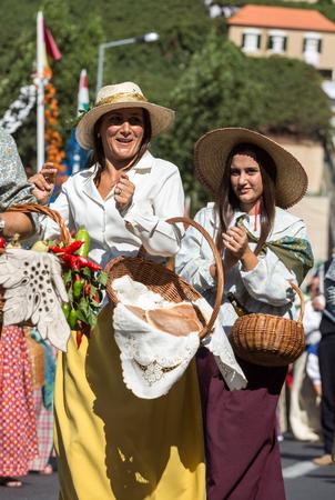 historical events: ESTREITO DE CAMARA DE LOBOS, PORTUGAL - SEPTEMBER 10, 2016: Women wearing in traditional costumes at Madeira Wine Festival in Estreito de Camara de Lobos, Madeira, Portugal. The Madeira Wine Festival honors the grape harvest with a celebration of traditio