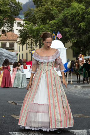 historical events: FUNCHAL, MADEIRA, PORTUGAL - SEPTEMBER 4, 2016:  Woman in historical fashion dress durnig historical and ethnographic  parade of Madeira Wine Festival in Funchal. Madeira, Portugal