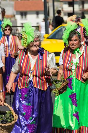 ESTREITO DE CAMARA DE LOBOS, PORTUGAL - SEPTEMBER 10, 2016: Women wearing in colorful costumes at Madeira Wine Festival in Estreito de Camara de Lobos, Madeira, Portugal. The Madeira Wine Festival honors the grape harvest with a celebration of traditional
