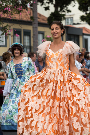 FUNCHAL, MADEIRA, PORTUGAL - SEPTEMBER 4, 2016:  Woman in historical fashion dress durnig historical and ethnographic  parade of Madeira Wine Festival in Funchal. Madeira, Portugal
