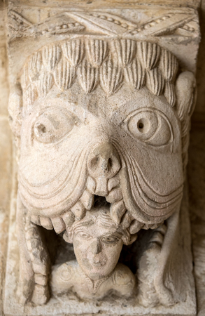 devouring: MONTMAJOUR, FRANCE - JUNE 26, 2017:  Monster or Tarasque Devouring a Sinner c12th Romanesque Carving in the Cloisters Montmajour Abbey near Arles Provence France Editorial