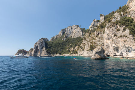 CAPRI, ITALY - JUNE 13, 2017: View from the boat on the Boats with tourists and the cliff coast of Capri Island. Italy
