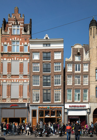 AMSTERDAM, NETHERLANDS - APRIL 20, 2017: Damrak main street crowded with tourists in Amsterdam, Netherlands