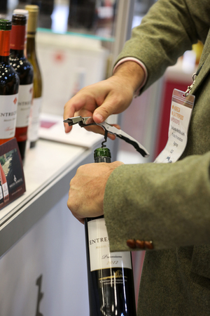 CRACOW POLAND - NOVEMBER 16 2017: International Wine Trade Fair ENOEXPO in Cracow. Man's Hands Opening Wine Bottle with Corkscrew