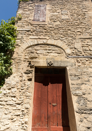 Old wooden door on stone  house  in Gordes. Provence, France