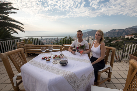 Sorrento, Italy - June 15, 2017: A happy couple at dinner on a terrace overlooking the bay of Naples and Mount Vesuvius. Sorrento. Italy Editorial