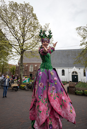 Noordwijkerhout, Netherlands - April 21,  2017: Women in colorful dresses walking on stilts  at the traditional flowers parade Bloemencorso from Noordwijk to Haarlem in the Netherlands Editöryel