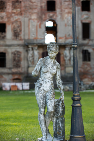 Brody, Poland - April 17, 2017: A stone sculpture of a woman on the background of  the Bruhl palace in Brody destroyed by the Soviet Army