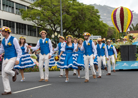Funchal, Madeira, Portugal - April 22, 2018 : A group of people in colorful costumes are dancing at Madeira Flower Festival Parade in Funchal on the Island of Madeira. Portugal. Foto de archivo - 100571197