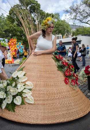 Funchal; Madeira; Portugal - April 22; 2018: The last moments before the parade, The parade participant dresses a wicker costume at the Madeira Flower Festival , Funchal, Madeira, Portugal Редакционное