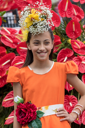 Funchal; Madeira; Portugal - April 22; 2018: The last moments before the parade, girl in a orange dress at the Madeira Flower Festival , Funchal, Madeira, Portugal