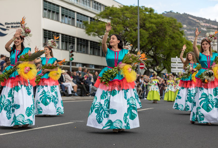 Funchal; Madeira; Portugal - April 22; 2018: A group of people in colorful costumes are dancing at Madeira Flower Festival Parade in Funchal on the Island of Madeira. Portugal. Editorial