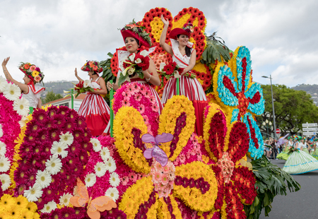 Funchal; Madeira; Portugal - April 22; 2018: A group of women in colorful costumes on the floral float at Madeira Flower Festival Parade in Funchal on the Island of Madeira. Portugal.