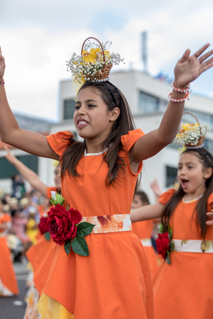 Funchal; Madeira; Portugal - April 22; 2018: A group of girls in orange costumes are dancing at Madeira Flower Festival Parade in Funchal on the Island of Madeira. Portugal. Editorial