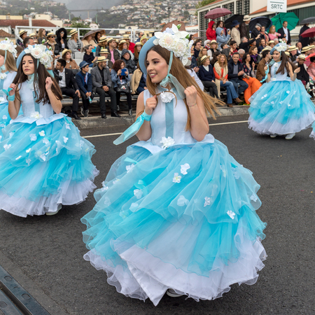 Funchal; Madeira; Portugal - April 22; 2018: A group of women in blue dresses are dancing at Madeira Flower Festival Parade in Funchal on the Island of Madeira. Portugal. Foto de archivo - 101774869